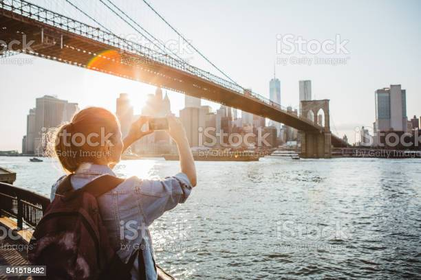 Woman photographing New York skyline at dusk