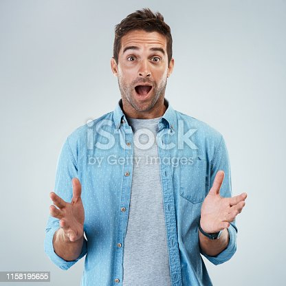 Portrait of a surprised facial expression standing against a grey background
