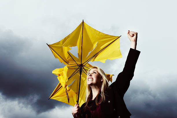 That's enough! Blonde with ruined umbrella shakes fist at thunderstorm A blonde woman with a frayed and broken umbrella shakes her fist at the thunderstorm that has ruined it. angry shaking fist stock pictures, royalty-free photos & images