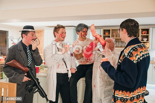 Group of work friends dressed up and laughing at a Halloween party. One of the men is holding up a leg prop as he pretends to drink from it.
