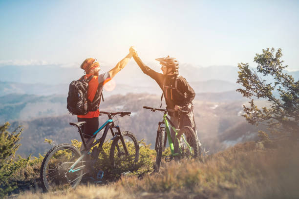 Thats ride was awesome,  two mountain bikers on a mountain peak Two young mans on a mountain, thats ride was awesome, feeling happy and smiling with the sun. mountain biking stock pictures, royalty-free photos & images