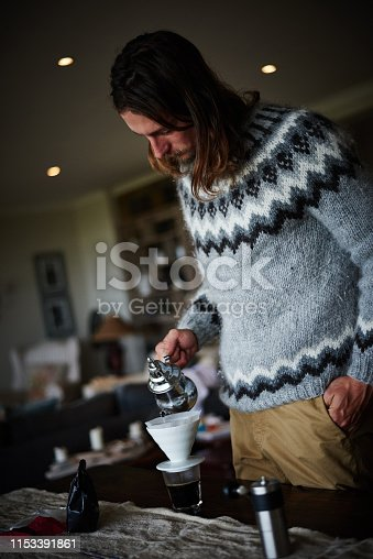 Shot of a young man preparing coffee in his kitchen
