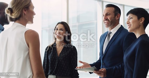 Cropped shot of a diverse group of businesspeople standing in the office together and having a discussion