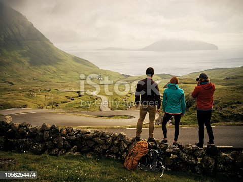 Rearview shot of a group of young friends standing next to each other while looking at a breathtaking view of a lake with an island in the middle outside during the day