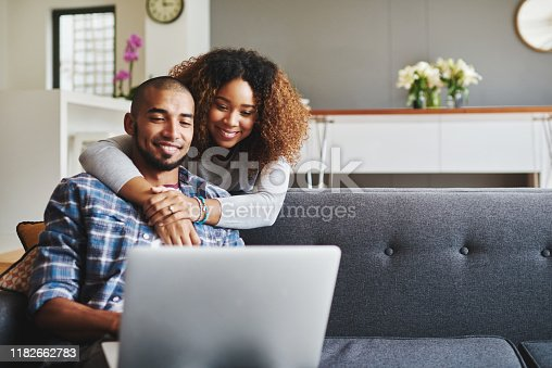 Cropped shot of an affectionate young couple sitting on the sofa together and using a laptop in their living room
