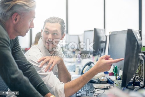 Businessmen reviewing some financial work at the desktop computer.