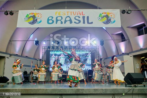 Tokyo, Japan - July 20, 2019: Brazilian people and Japanese people giving Brazilian percussion music performance show on the stage against LED light screen at Yoyogi Park during the 14th Festival Brasil. It is an annual admission free event hold in July every year.