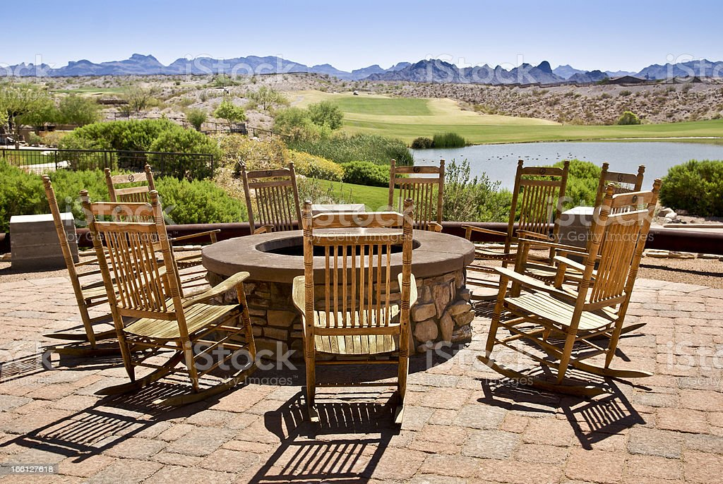 The 19th Hole Wooden rocking chairs, surrounding a firepit invite conversation beside a golf course and a pond. Arranging Stock Photo