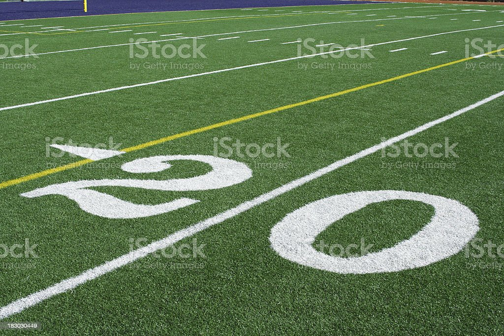 Heavy white numbers painted on artificial turf at the 20 yard line of...