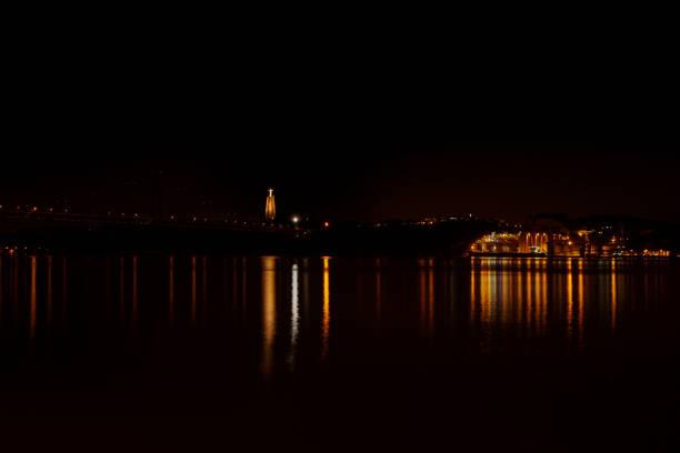 the 25th april bridge in lisbon, portugal crossing the tagus river at night. on left is the cristo rei statue - cristo rei lisboa imagens e fotografias de stock