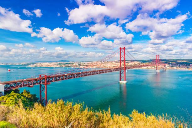 The 25th April Bridge (Ponte 25 de Abril) in Lisbon, Portugal. Picturesque skyline with beautiful sky stock photo
