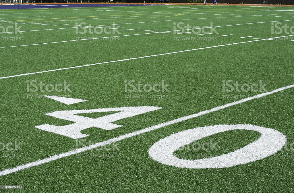 Heavy white numbers painted on artificial turf at the 40 yard line of...