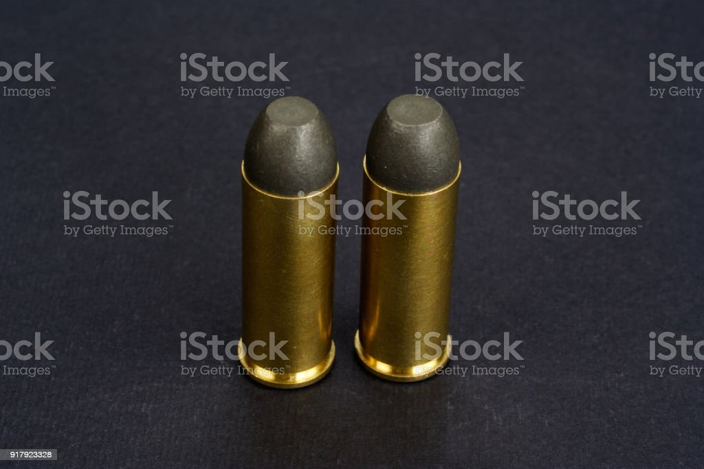 The .45 caliber revolver cartridges on black background stock photo