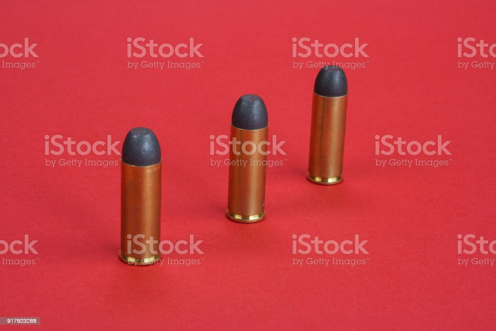 The .45 caliber revolver cartridges on red background stock photo
