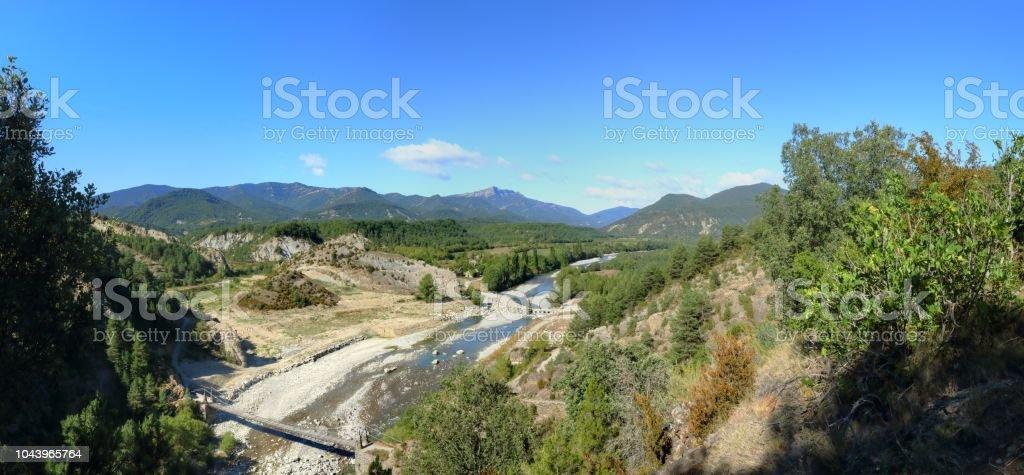 El paisaje con el puente de madera para llegar a Janovas, una aldea arruinada en el Pirineo Aragonés abandonado durante los años sesenta debido a la construcción de una presa - foto de stock