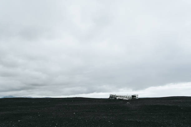 The abandoned wrecked plane amidst black sand in Iceland. Grey cloud sky. The abandoned wrecked plane amidst black sand in Iceland. Grey cloud sky. sólheimasandur stock pictures, royalty-free photos & images