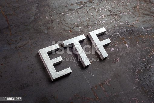 the abbreviation word etf - Exchange Traded Fund - laid with silver letters on raw rusted steel sheet surface in slanted diagonal perspective.