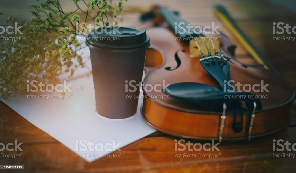 The abstract art design background of classic violin and bow put on wooden timber ground floor,beside mobile phone and black coffee cup royalty-free stock photo