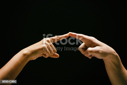 1035928092istockphoto The abstract art design background of human fingers touch together,sign and symbol of the love couple,romantic feeling between man and woman ,vintage and art style,classic tone,blurry light around. 959542860