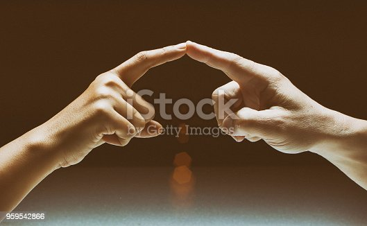 1035928092istockphoto The abstract art design background of human fingers touch together,sign and symbol of the love couple,romantic feeling between man and woman ,vintage and art style,classic tone,blurry light around. 959542866