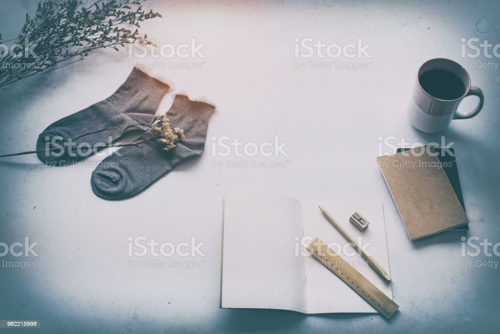 The abstract art design background of the opened book put at the middle of socks and ceramic coffee cup,on table,blurry light around. stock photo