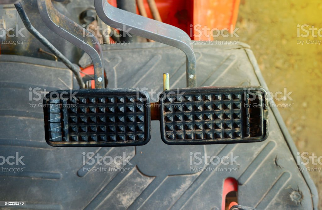 The accelerate and break pedals on tractor stock photo