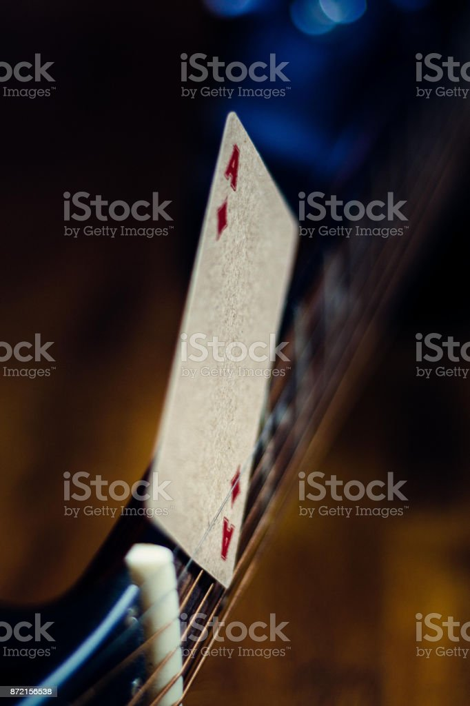 The ace of spades is clamped between the strings of a guitar. – zdjęcie