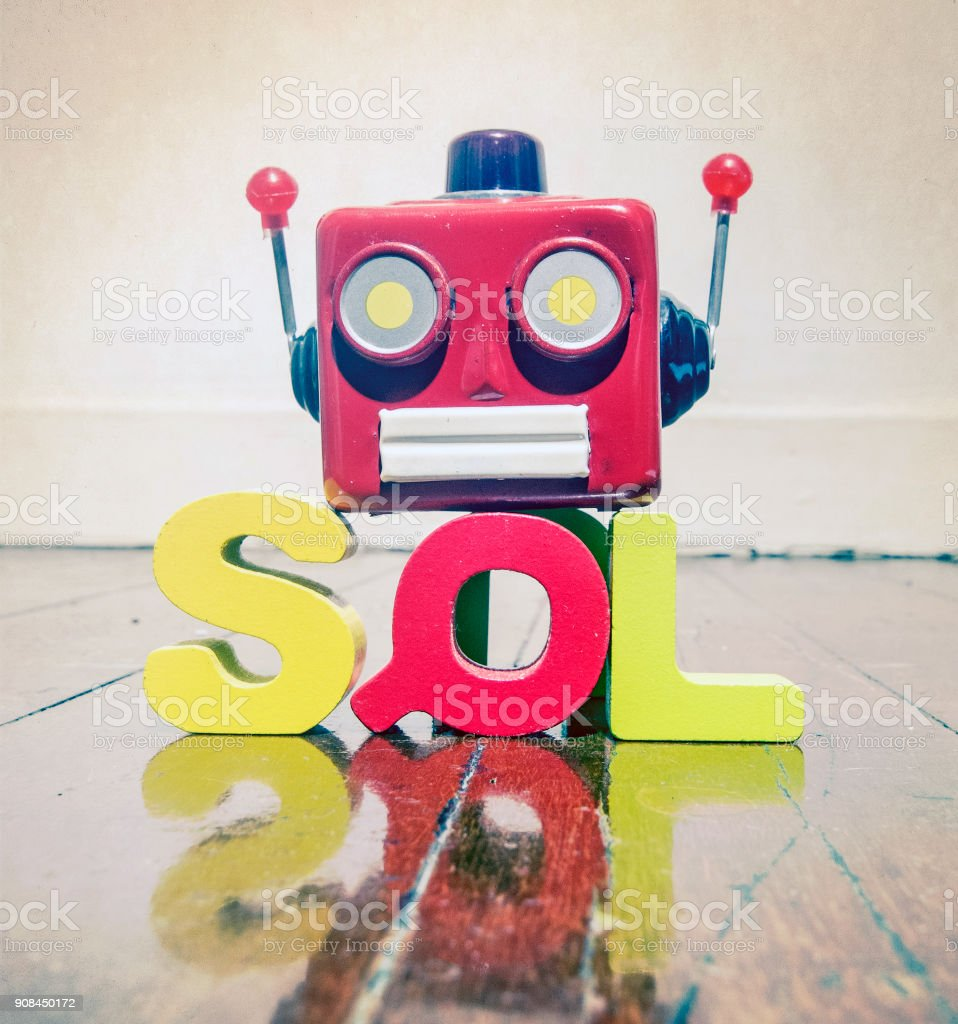 the acronym SQL with a robot head  on a wooden floor with reflection stock photo