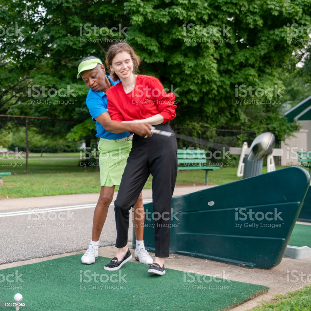 The active 77-years-old senior African-American woman teaching the 18-years-old Caucasian girl to play golf. – zdjęcie