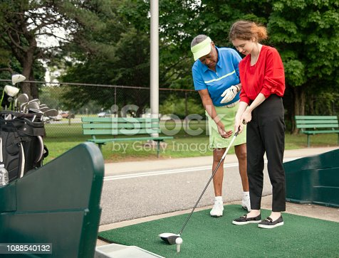 istock The active 77-years-old senior African-American woman teaching the 18-years-old Caucasian girl to play golf. 1088540132