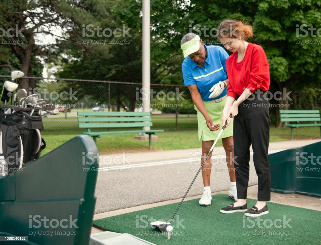 A ativa 77 anos sênior afro-americana ensinando a branquela de 18 anos de idade para jogar golfe. - foto de acervo