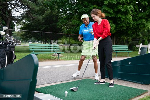istock The active 77-years-old senior African-American woman teaching the 18-years-old Caucasian girl to play golf. 1088540134
