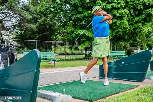 The active, optimistic 77-years-old senior Black African-American woman practicing golf. Long Island, New York State, USA