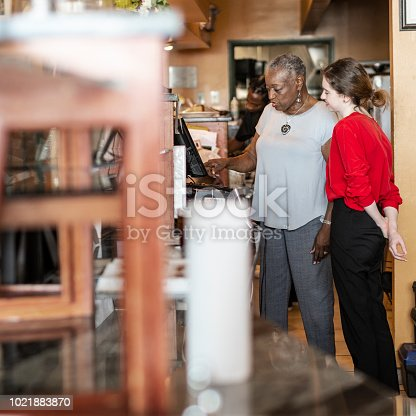 istock The active senior, 77-years-old, African-American businesswoman, business owner, teaching the new employee, the 18-years-old Caucasian white girl, how to use the computerized cash register in the small local restaurant. 1021883870