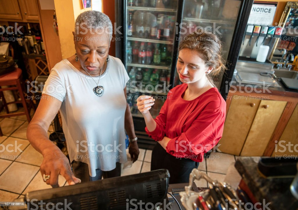 O ativo sênior, Africano-americano, de 77 anos de idade mulher de negócios, proprietário da empresa, ensinando o novo empregado, o caucasiano de 18 anos de idade menina branca, como usar a caixa registradora informatizada no pequeno restaurante local. - foto de acervo