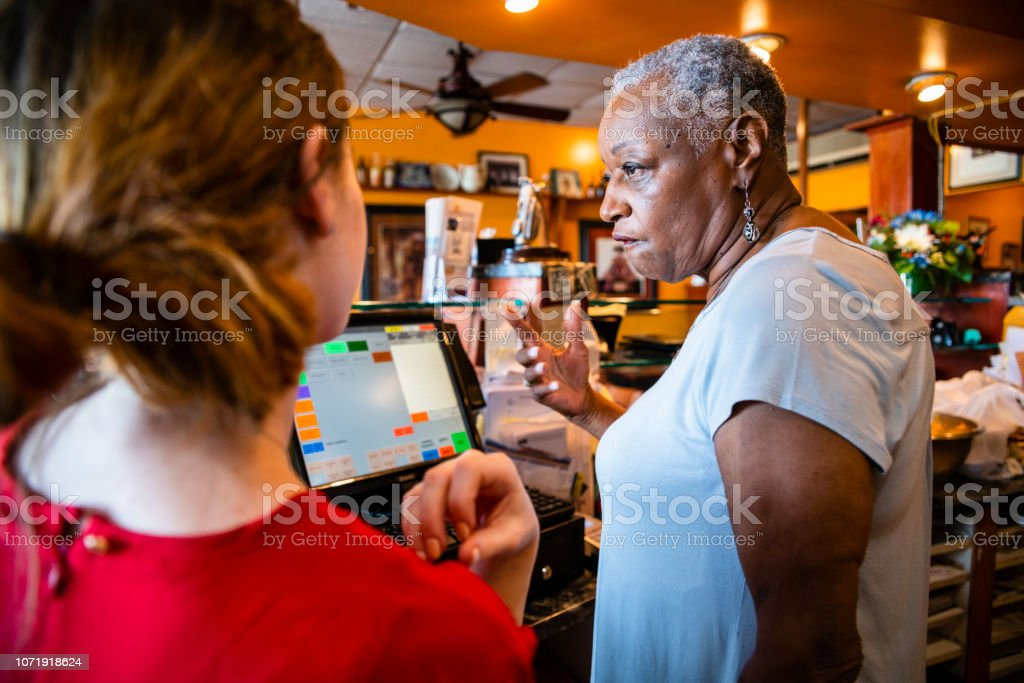 The active senior, 77-years-old, African-American businesswoman, business owner, teaching the new employee, the 18-years-old Caucasian white girl, how to use the computerized cash register in the small local restaurant. – zdjęcie