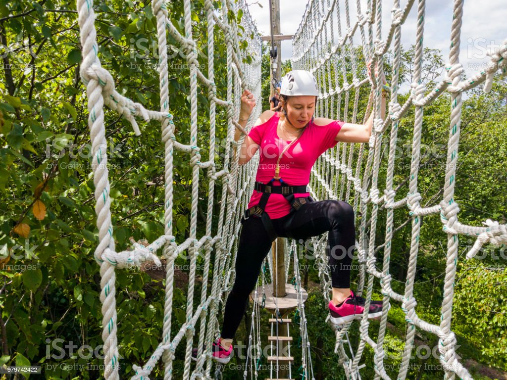 The adult woman passing the zip line. Mobile photo. stock photo