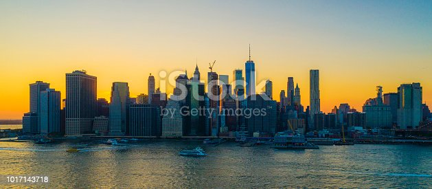 The aerial scenic panoramic view to Manhattan Downtown from Brooklyn over the East River at the sunset. The clean hot summer evening, twilight time.