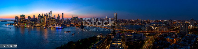 The aerial scenic panoramic view to illuminated Manhattan Downtown from Brooklyn Heights over the East River at the sunset. The clean hot summer evening, twilight time.