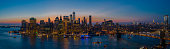 The aerial scenic panoramic view to illuminated Manhattan Downtown from Brooklyn over the East River at the sunset. The clean hot summer evening, twilight time.