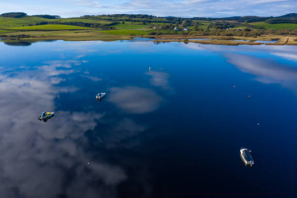 The aerial view from a drone of a slow moving stretch of water in rural Dumfries and Galloway south west Scotland The view from a drone of a stretch of Scottish river that is flowing out out of a loch. It is early autumn and autumn colours are stating to show on the plants and trees. johnfscott stock pictures, royalty-free photos & images