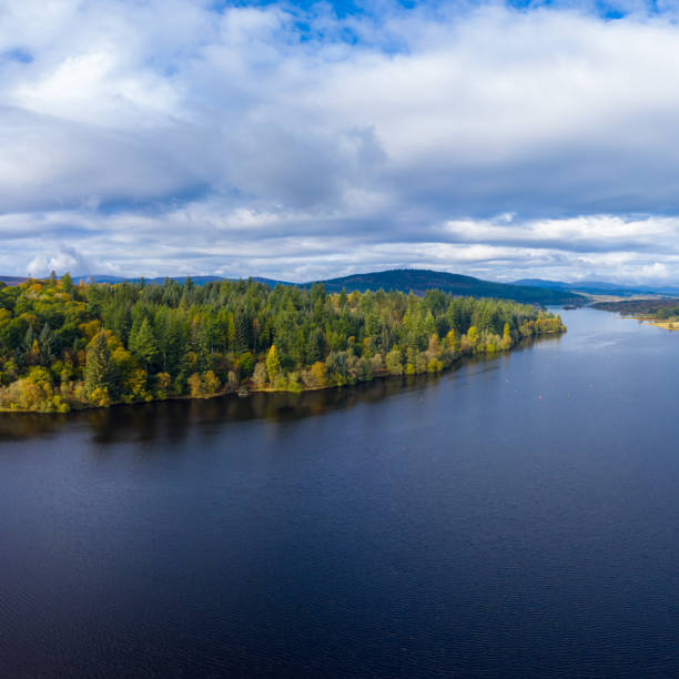 The aerial view from a drone of forest growing beside a Scottish loch in Dumfries and Galloway south west Scotland. The view from a drone as it is flown over a Scottish loch towards mixed woodland. The image was captured on an autumn morning, some of the trees have started to show their autumn colours. The panorama was created by merging several images together. johnfscott stock pictures, royalty-free photos & images