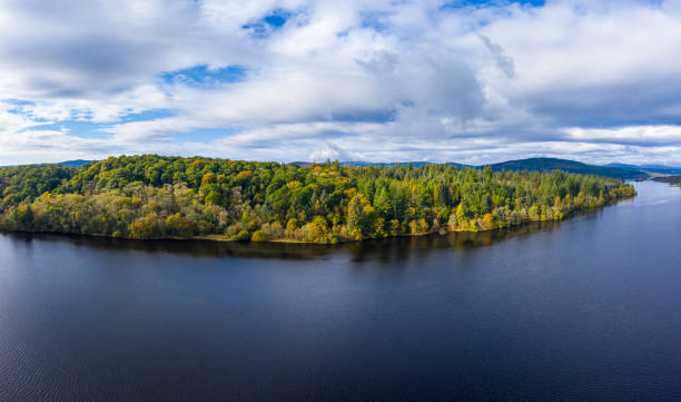 The aerial view of a Scottish loch and forest in Dumfries and Galloway south west Scotland. The view from a drone as it is flown over a Scottish loch towards mixed woodland. The image was captured on an autumn morning, some of the trees have started to show their autumn colours. The panorama was created by merging several images together. johnfscott stock pictures, royalty-free photos & images