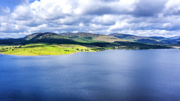The aerial view of a Scottish loch captured from a drone on a bright summer day The high angle view across a loch towards a range of hills in Dumfries and Galloway, south west Scotland. The fresh water reservoir is part of the Galloway Hydro Electric Power scheme. johnfscott stock pictures, royalty-free photos & images