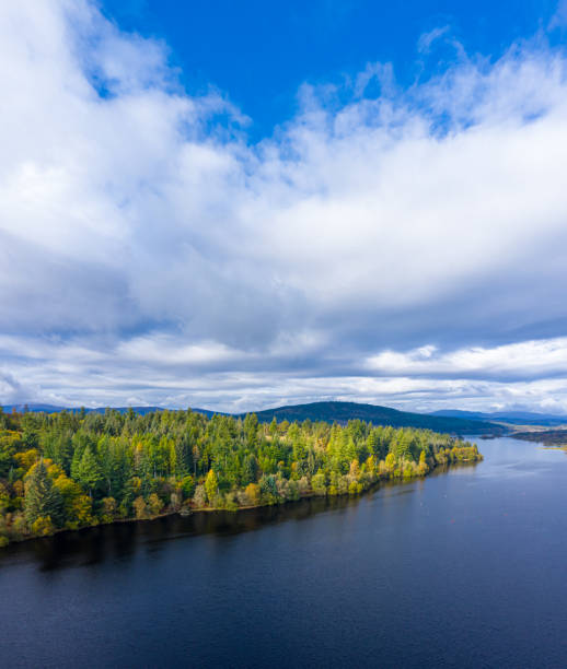 The aerial view of a slow moving river and forest in rural Dumfries and Galloway south west Scotland The view from a drone of a stretch of Scottish river that is flowing out out of a loch. It is early autumn and autumn colours are stating to show on the plants and trees. The panorama was created by merging several images together. johnfscott stock pictures, royalty-free photos & images
