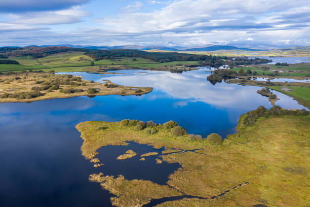 The aerial view of a slow moving river in Dumfries and Galloway south west Scotland The view from a drone of a stretch of Scottish river that is flowing out out of a loch. It is early autumn and autumn colours are stating to show on the plants and trees. johnfscott stock pictures, royalty-free photos & images