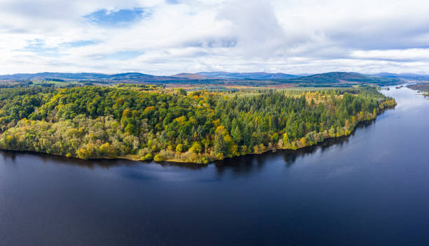 The aerial view of a slow moving river in rural Dumfries and Galloway south west Scotland The view from a drone of a stretch of Scottish river that is flowing out out of a loch. It is early autumn and autumn colours are stating to show on the plants and trees. The panorama was created by merging several images together. johnfscott stock pictures, royalty-free photos & images
