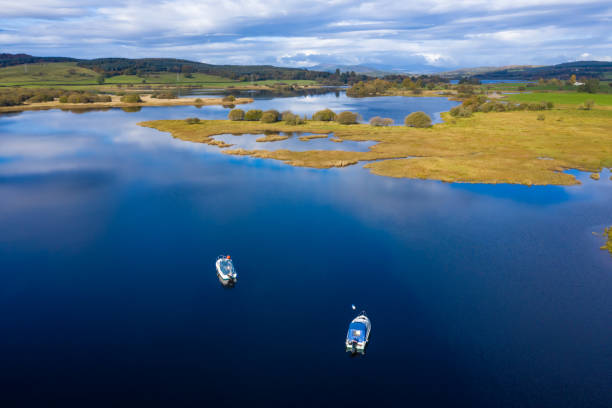 The aerial view of a slow moving river in rural Dumfries and Galloway south west Scotland The view from a drone of a stretch of Scottish river that is flowing out out of a loch. It is early autumn and autumn colours are stating to show on the plants and trees. johnfscott stock pictures, royalty-free photos & images