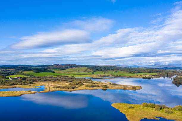 The aerial view of a slow moving stretch of water in rural Dumfries and Galloway south west Scotland The view from a drone of a stretch of Scottish river that is flowing out out of a loch. It is early autumn and autumn colours are stating to show on the plants and trees. johnfscott stock pictures, royalty-free photos & images