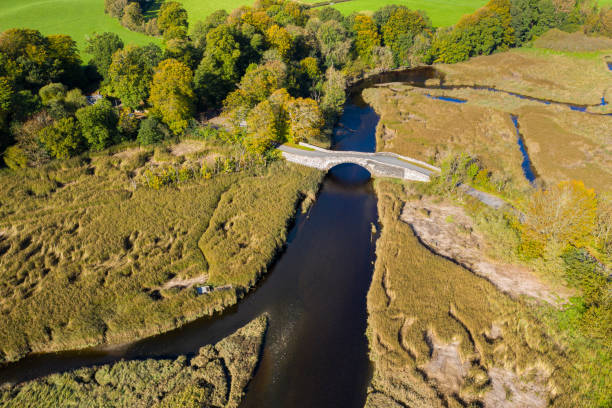 The aerial view of an old stone bridge in Dumfries and Galloway south west Scotland The view from a drone of an old stone bridge crossing a small river that flows into an estuary in Dumfries and Galloway, south west Scotland. johnfscott stock pictures, royalty-free photos & images